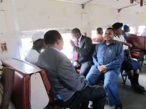 Minister of Transport, Dr. Harrison Mwakyembe (centre waving hand) accom­panied by officials from the Transportation Authority of Land Surface and Marine (Sumatra) on the first commuter train. Photo isaackin.blogspot